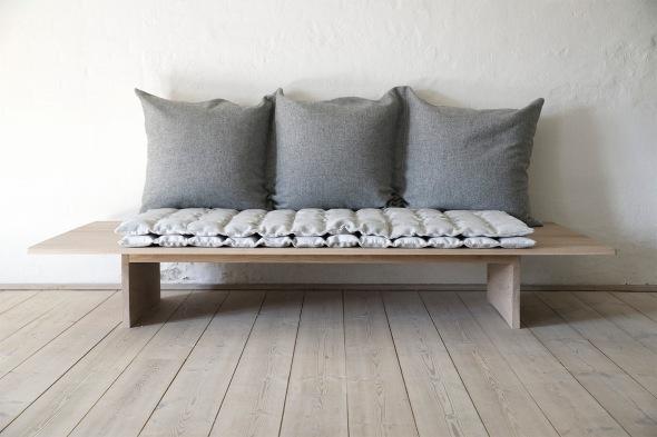 Briksen er placeret mod væggen, og de tre sammensatte puder læner op af og danner en dyb favnende komfortabel ryg.