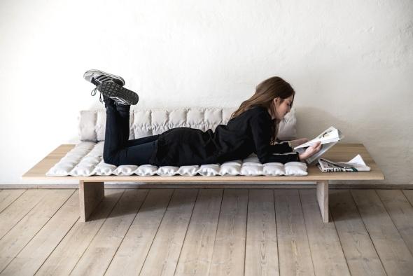 Delen til at sidde på er rullet sammen til den ene side, og danner en lav ryg mod væggen.